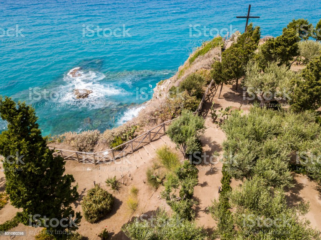 Aerial view of a cross on the promontory of the Sanctuary of Santa Maria dell'isola, Tropea, Calabria, Italy. Gardens of the sanctuary. Sea and waves stock photo