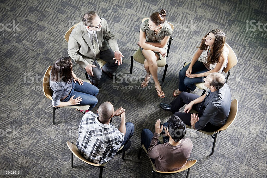 Aerial view of a diverse group sitting in a circle stock photo