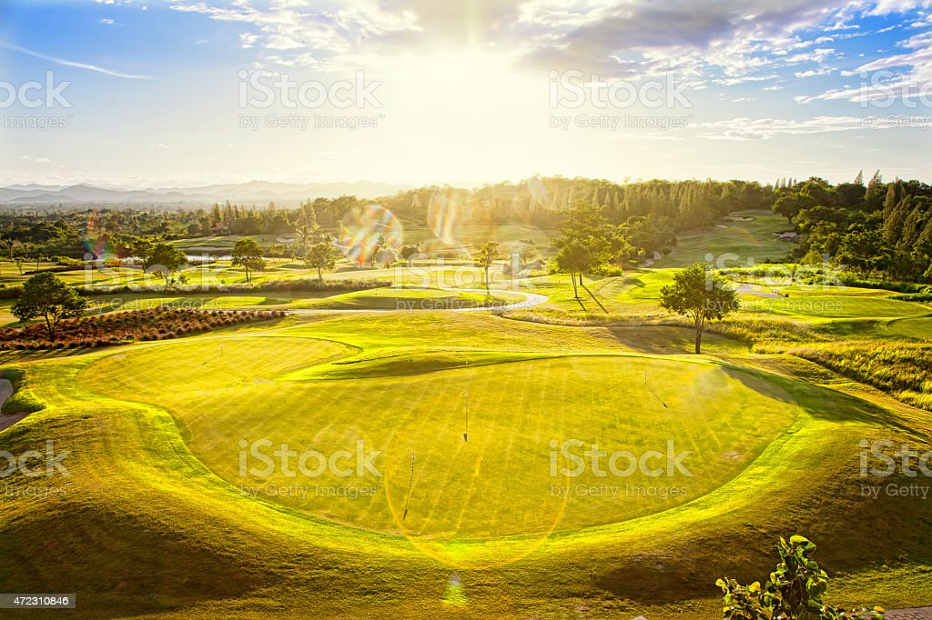Aerial view of a large green golf course with sun spots stock photo