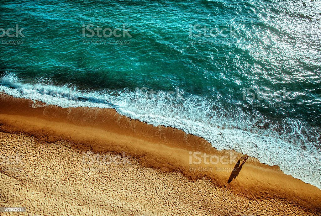 Aerial view of a surfer girl resting on a beach stock photo