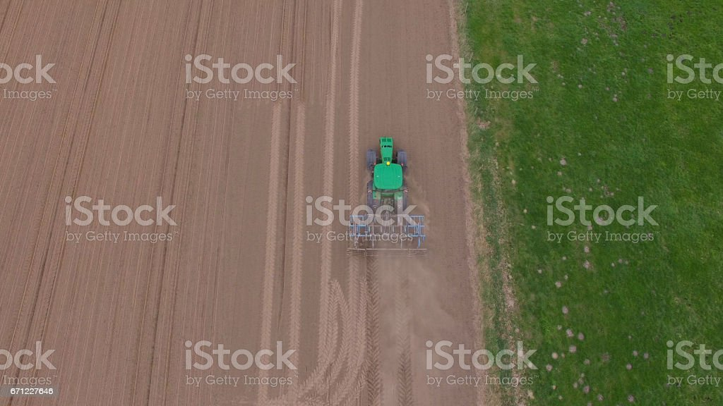 aerial view of a tractor at work - cultivating a field in spring - agricultural machinery stock photo