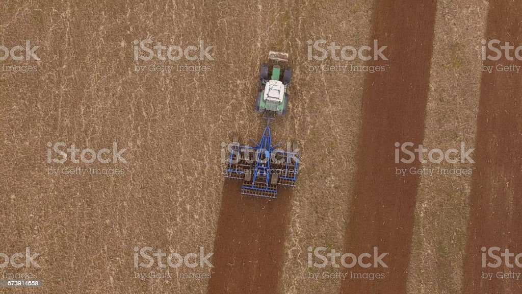aerial view of a tractor at work on a beautiful agricultural fields in spring - top view stock photo