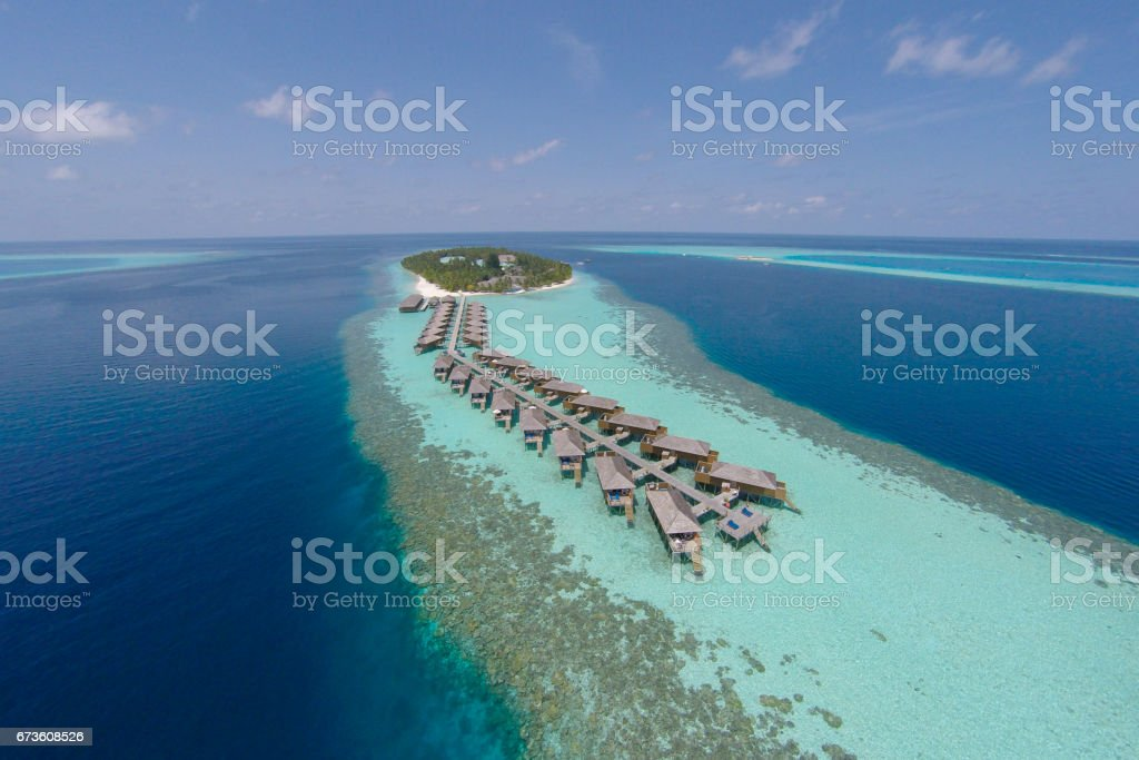 Aerial view of a tropical island in turquoise water. Luxurious over-water villas on tropical island resort maldives for holiday vacation background concept -Boost up color Processing. stock photo