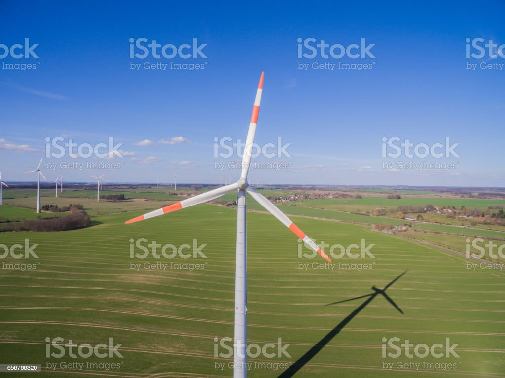 aerial view of a wind turbine in agriculture fields with blue sky stock photo