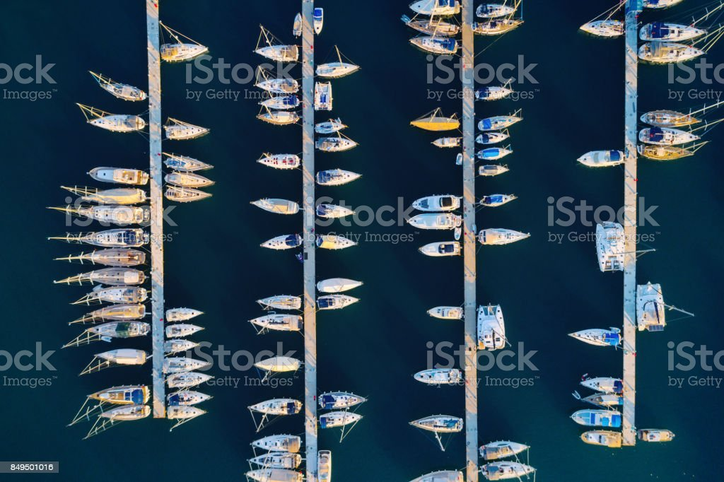 Aerial view of amazing boats at sunset in Marmaris, Turkey. Minimalistic landscape with boats and sea in marina bay. Top view from drone of harbor with yacht, motorboat and sailboat. Beautiful port stock photo