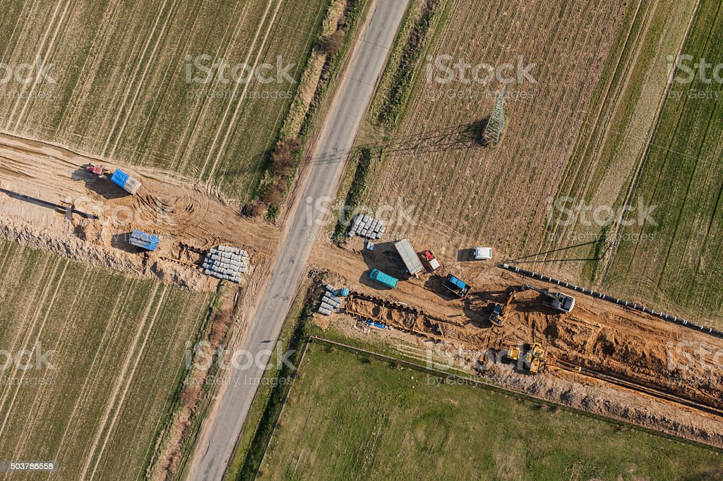 aerial view of burying gas pipe on the harvest fields stock photo