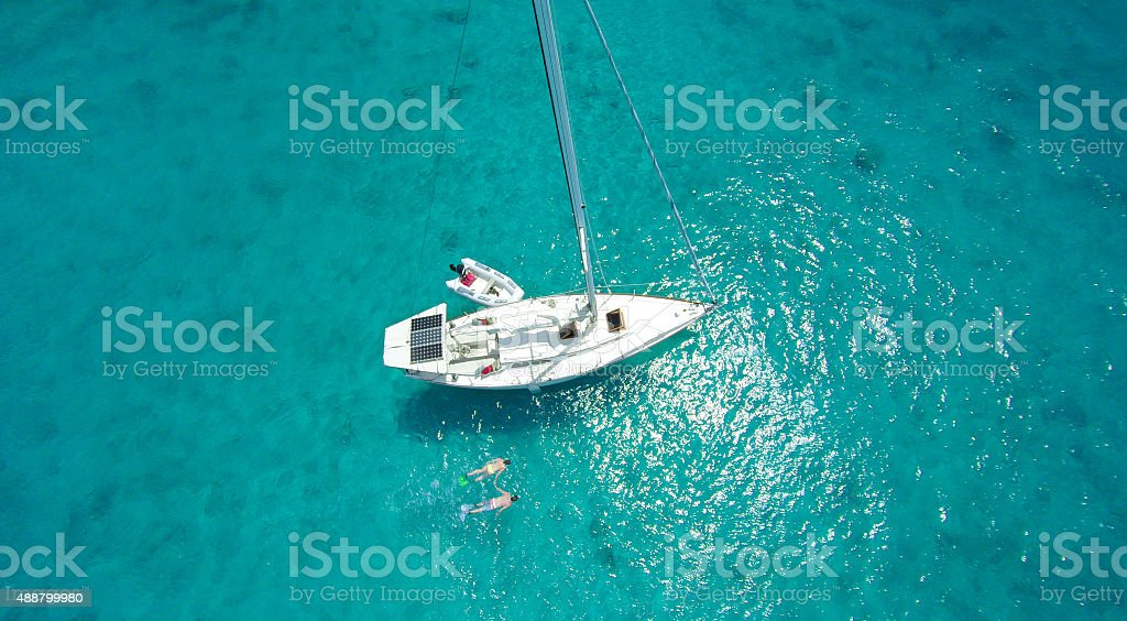 aerial view of couple snorkeling by sailboat in the Caribbean stock photo