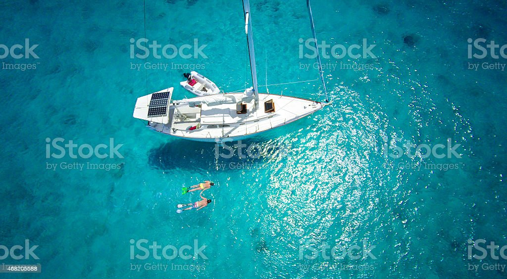 aerial view of couple snorkeling next to a luxury sailboat stock photo
