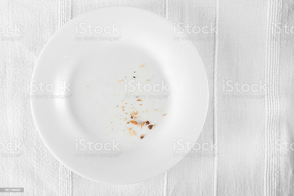 Aerial view of crumbs on a white dinner plate stock photo