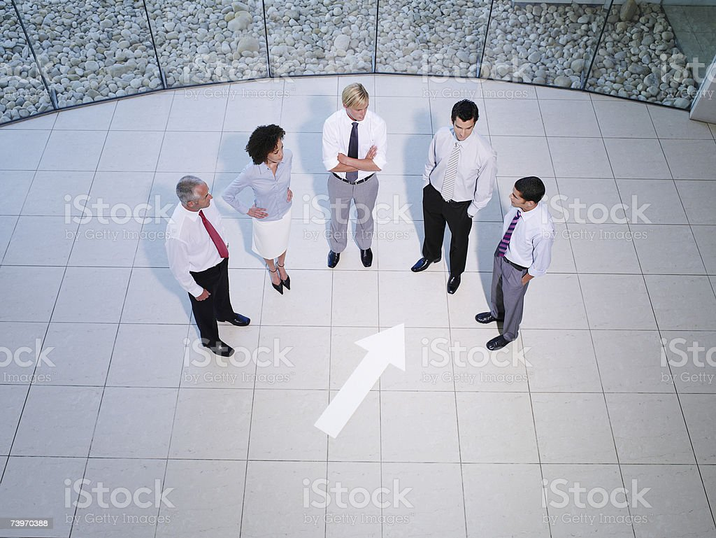 Aerial view of five office workers with pointing arrow sign on floor royalty-free stock photo
