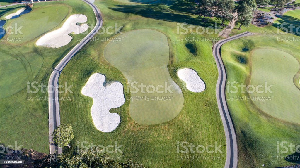 Aerial view of golf course green, bunkers and golf cart pathways stock photo