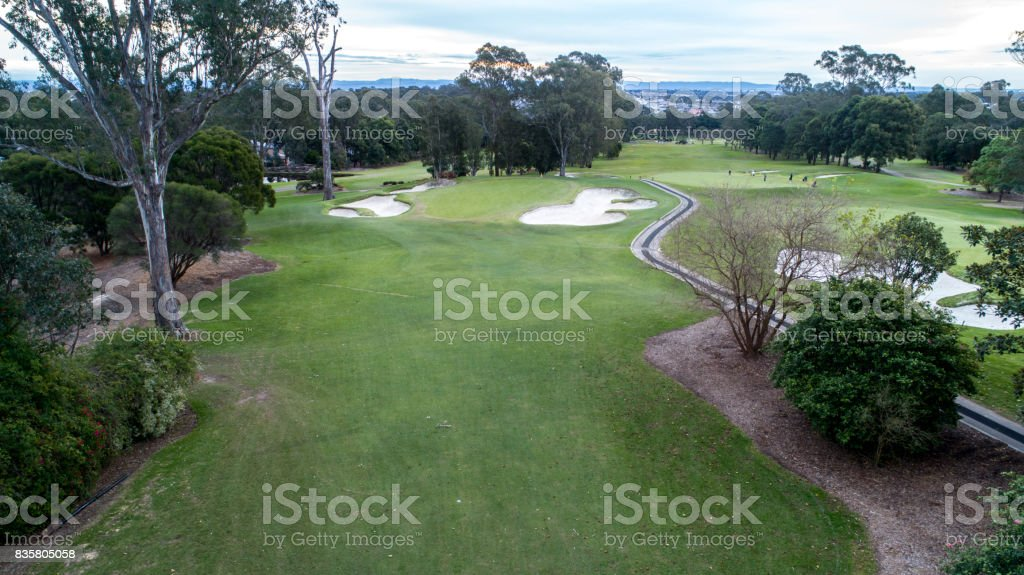 Aerial view of golf course tree lined fairway with green, bunkers and golf cart pathways stock photo
