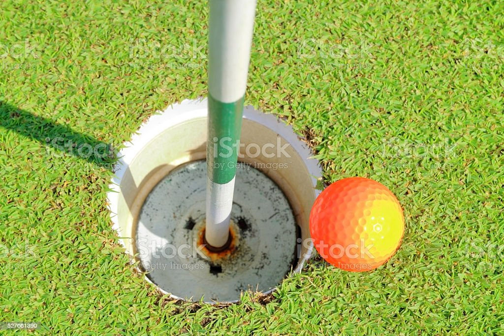 Aerial view of golf hole and ball on green grass. stock photo
