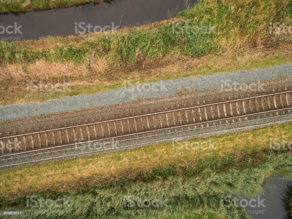 aerial view of green geometric agricultural field with railway stock photo