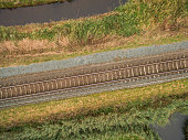 aerial view of green geometric agricultural field with railway