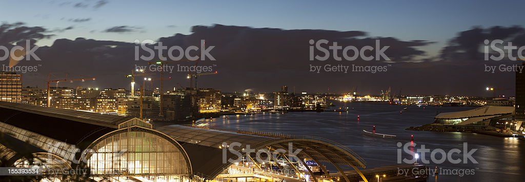 Aerial view of illuminated Amsterdam Central Station at dusk, panorama royalty-free stock photo