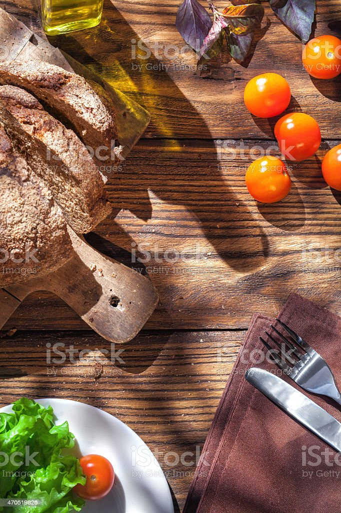 Aerial view of Italian bread and salad on wooden table stock photo