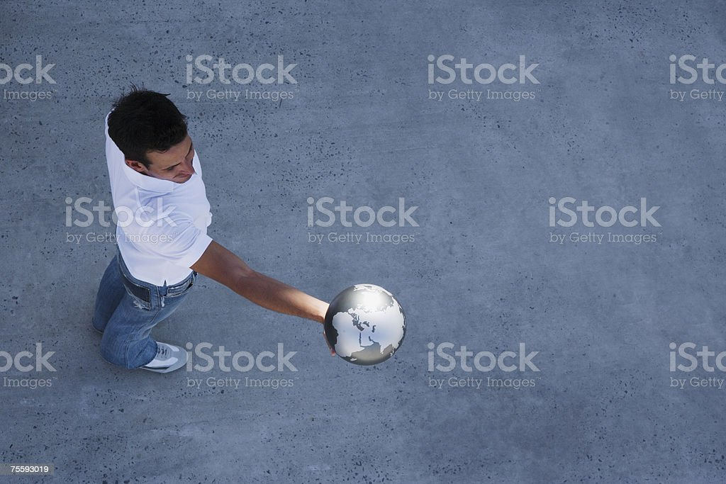 Aerial View of man holding globe outdoors stock photo