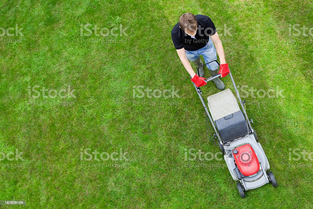 Aerial view of man on green lawn with push mower stock photo