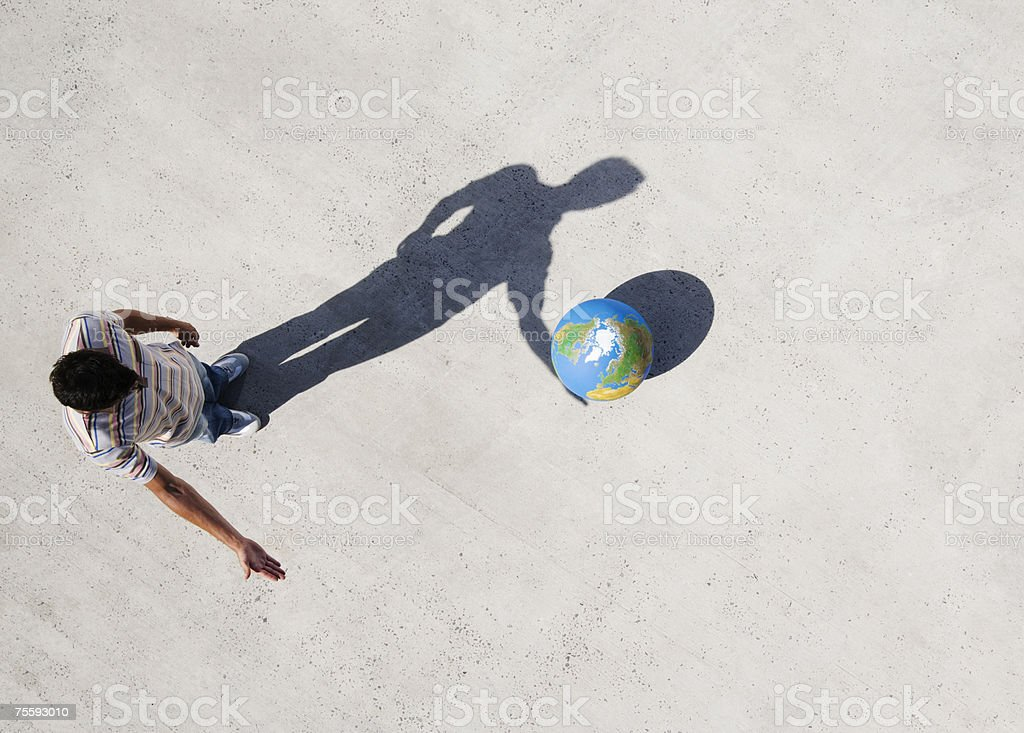 Aerial View of man with shadow and globe stock photo