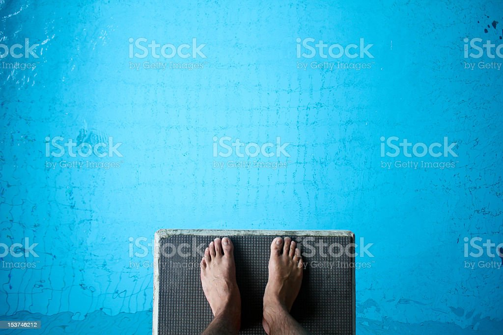 Aerial view of man's feet on diving board on blue stock photo
