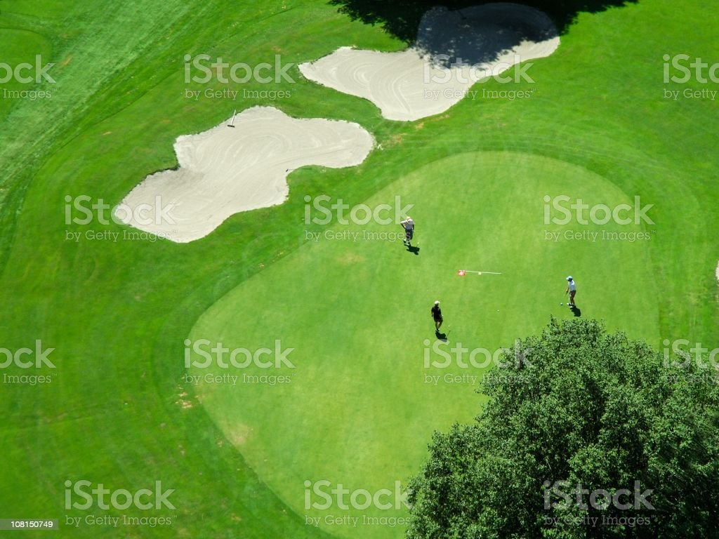 Aerial view of players on a green golf course stock photo