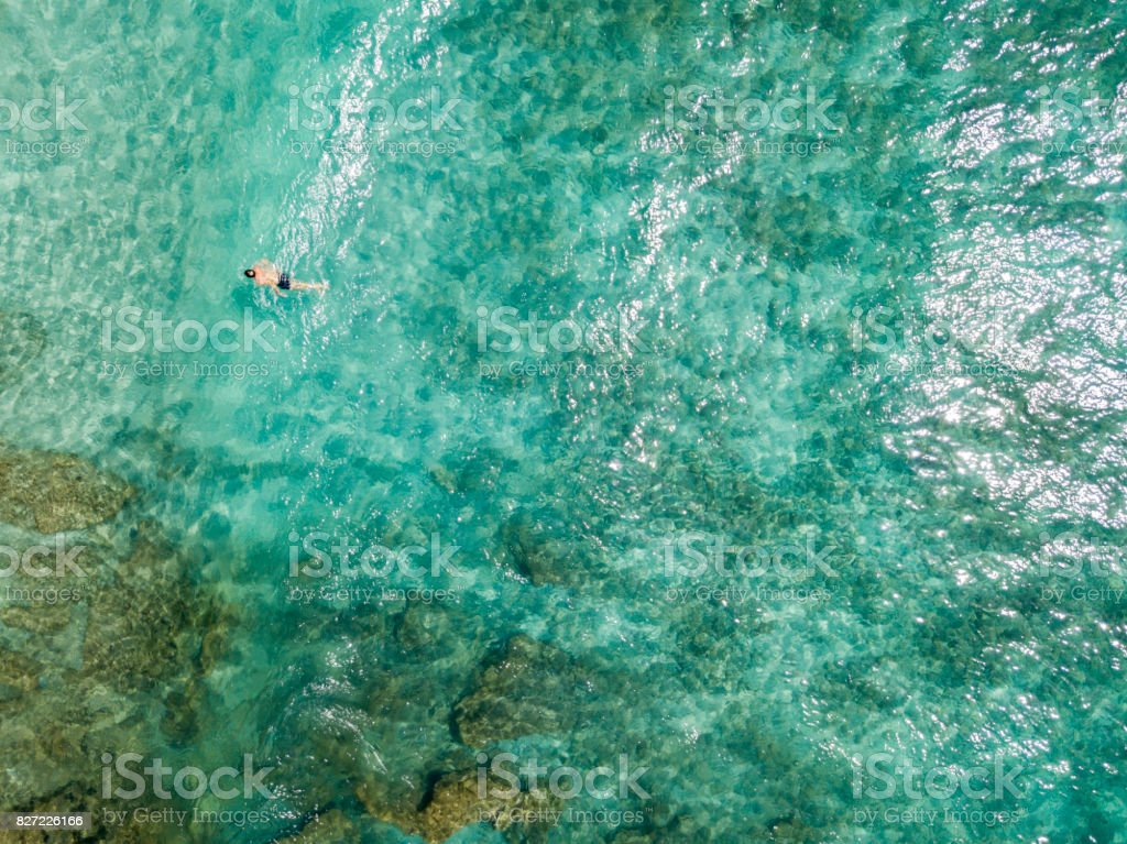 Aerial view of rocks on the sea. Overview of seabed seen from above, transparent water. Swimmers, bathers floating on the water stock photo