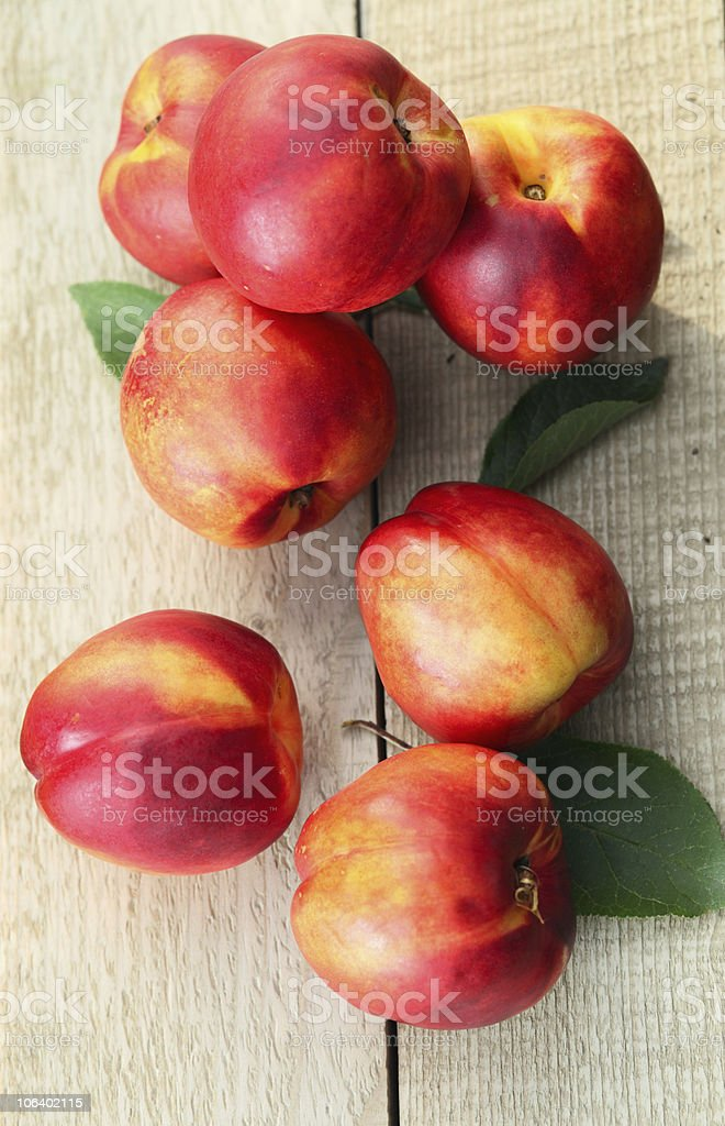 Aerial view of seven nectarines on a light wooden table stock photo