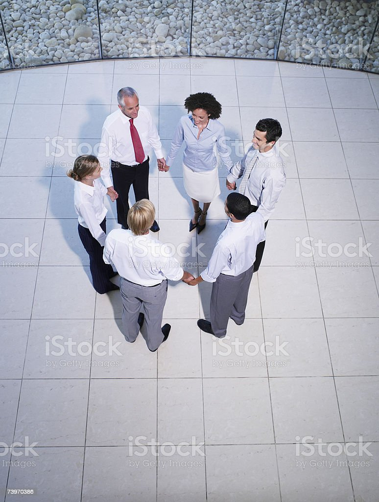 Aerial view of six office workers holding hands royalty-free stock photo
