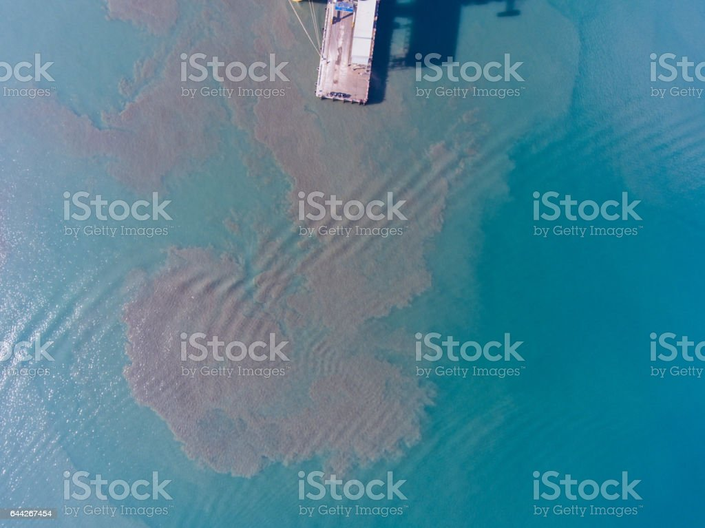Aerial view of the dirt in the water near the pier at the port stock photo