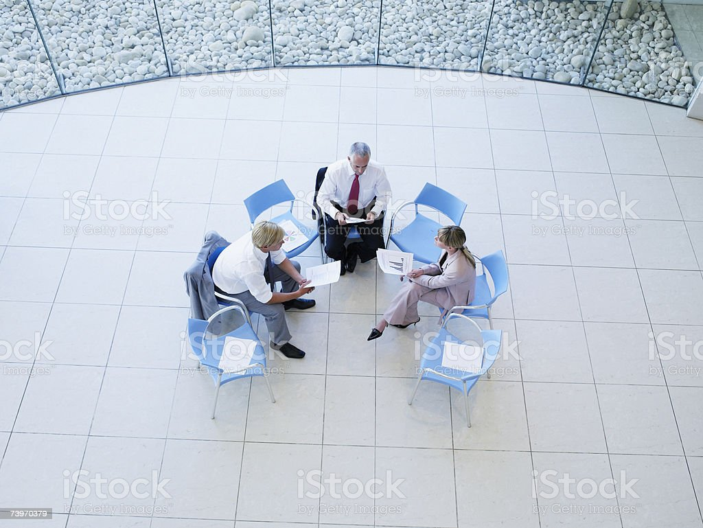 Aerial view of three office workers meeting in a rotunda stock photo
