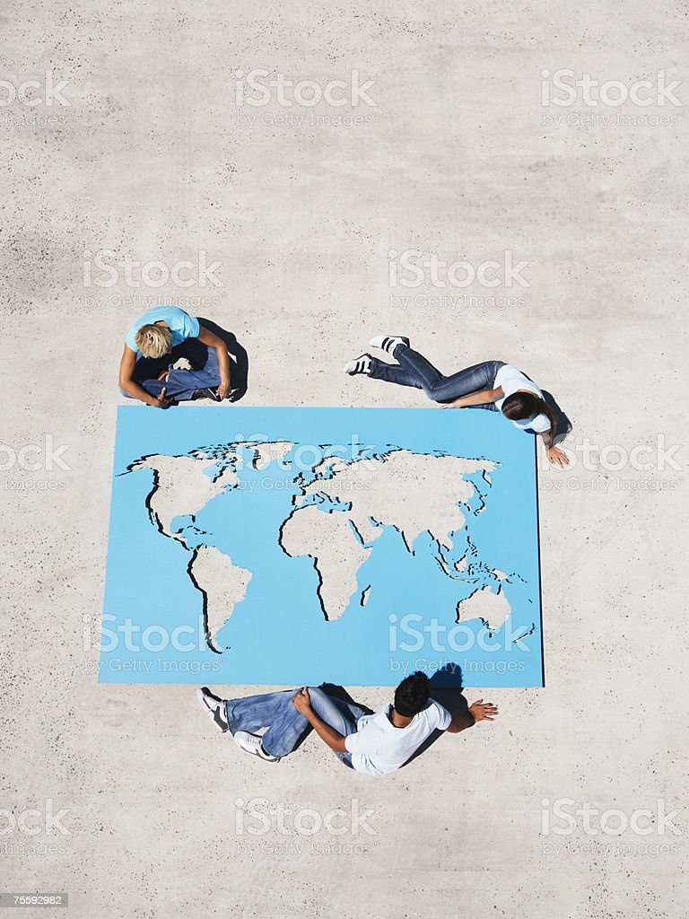 Aerial view of three people looking down at world map royalty-free stock photo