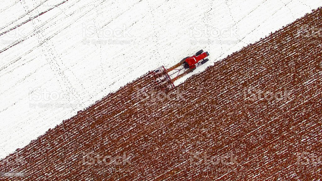 Aerial view of tractor tilling snow covered field in Winter stock photo