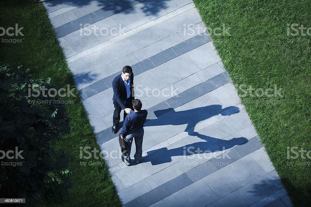 Aerial view of two businessmen shaking hands on the sidewalk stock photo