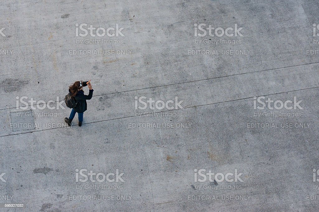 Aerial view of young woman taking photo with her smartphone stock photo