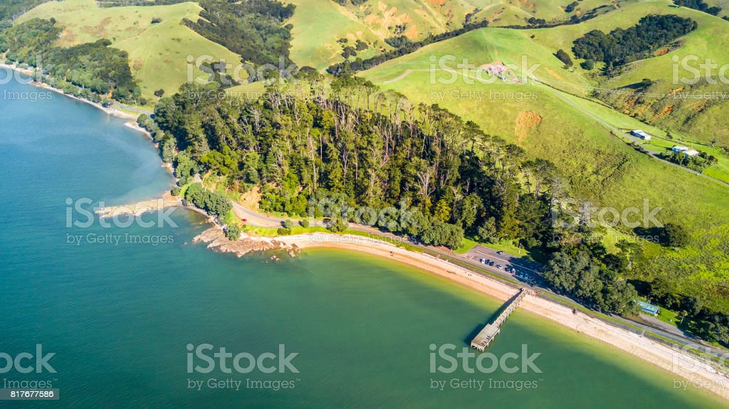 Aerial view on a sunny beach with small jetty and a car park along the road. Auckland, New Zealand stock photo