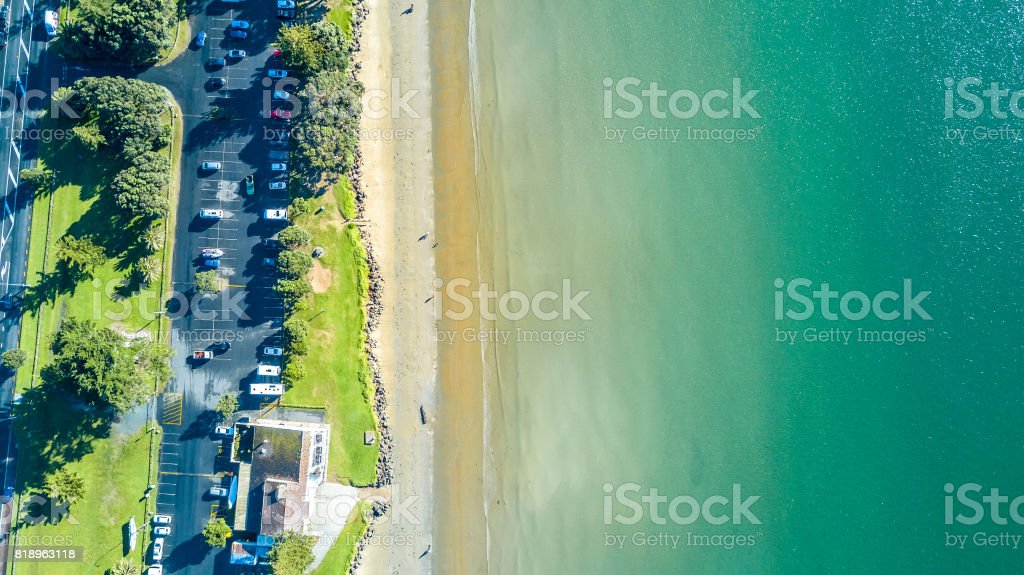 Aerial view on sunny beach with car parking. Auckland, New Zealand. stock photo