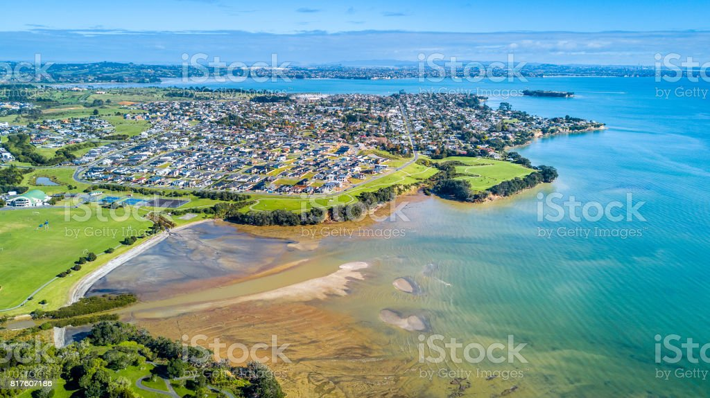 Aerial view on sunny beach with residential suburb on the background. Auckland, New Zealand. stock photo