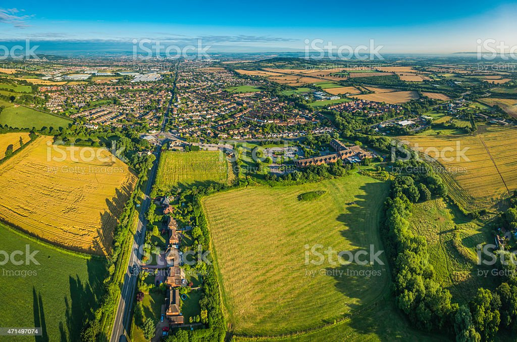 Aerial view over green fields pasture country town suburban housing stock photo