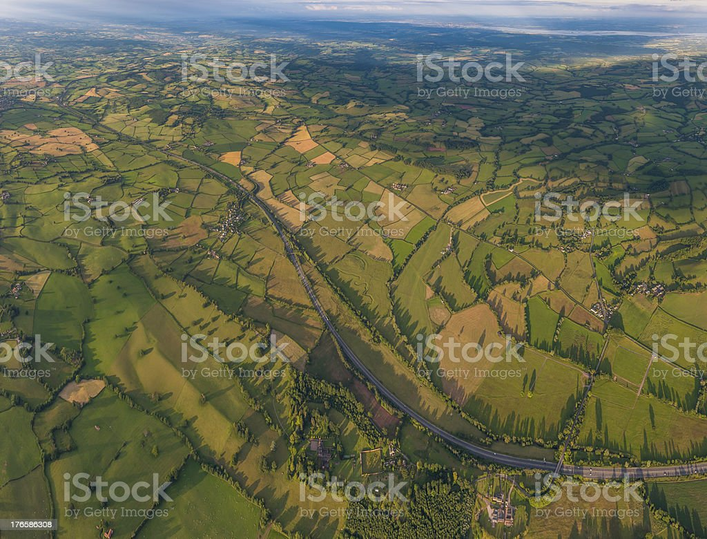 Aerial view over highway between green patchwork landscape royalty-free stock photo