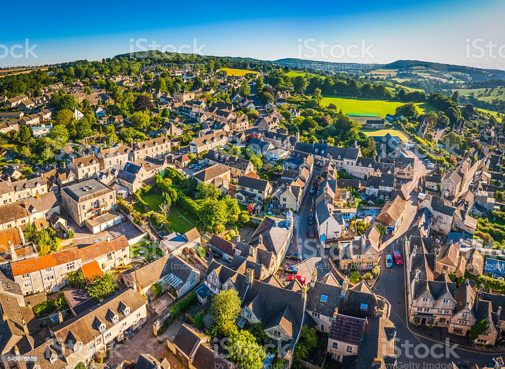 Aerial view over pretty rural village cottages summer fields Cotswolds stock photo