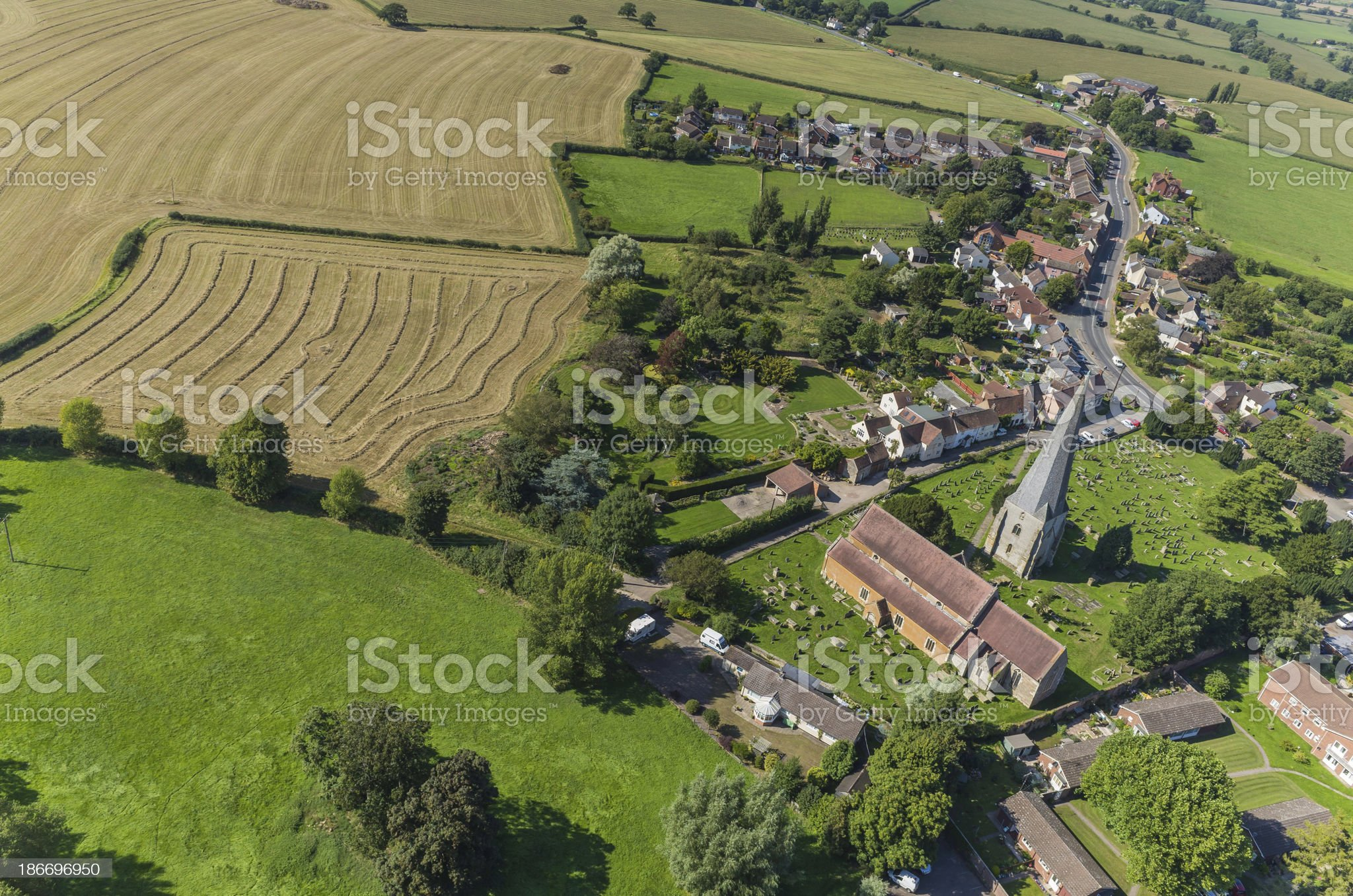 Aerial view over rural village crop fields church spire farms royalty-free stock photo