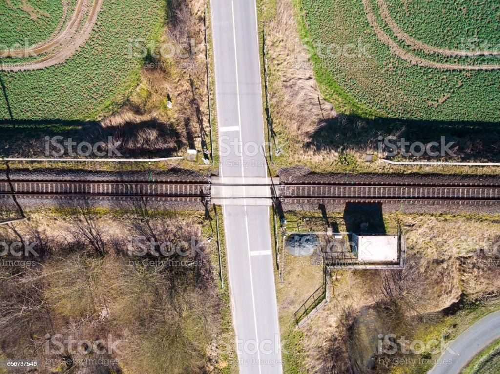 aerial view - top view of railroad tracks with railroad crossing in the countryside stock photo