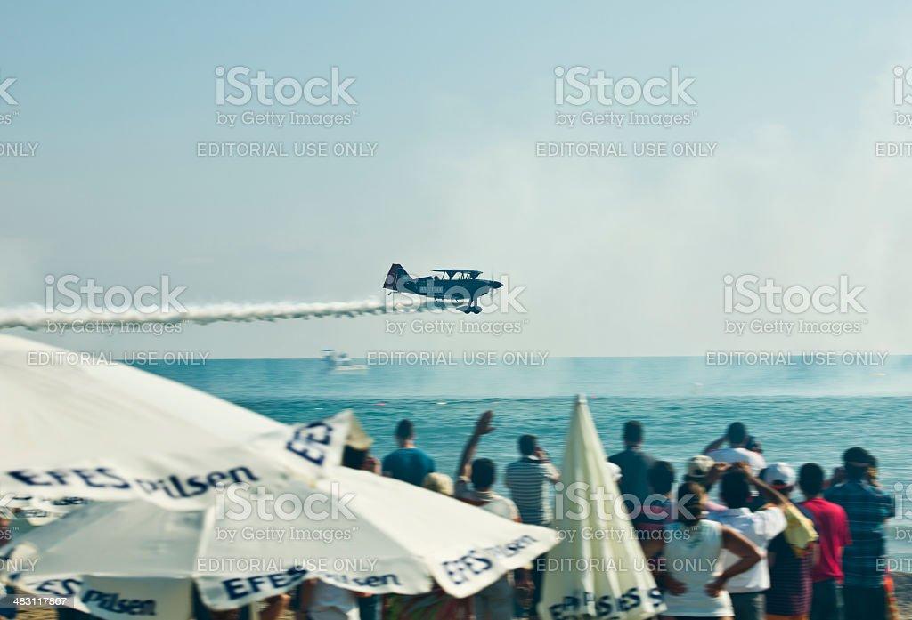 Aerobatic biplane flying with smoke over the sea. royalty-free stock photo