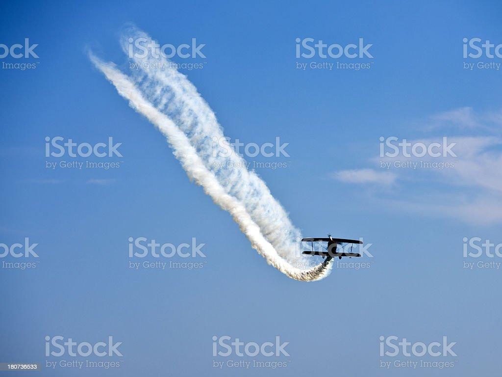 Aerobatic biplane flying with smoke royalty-free stock photo