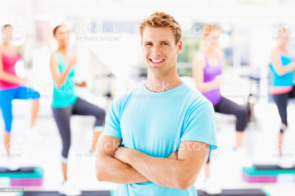 Aerobics Instructor With Class Exercising In Background stock photo