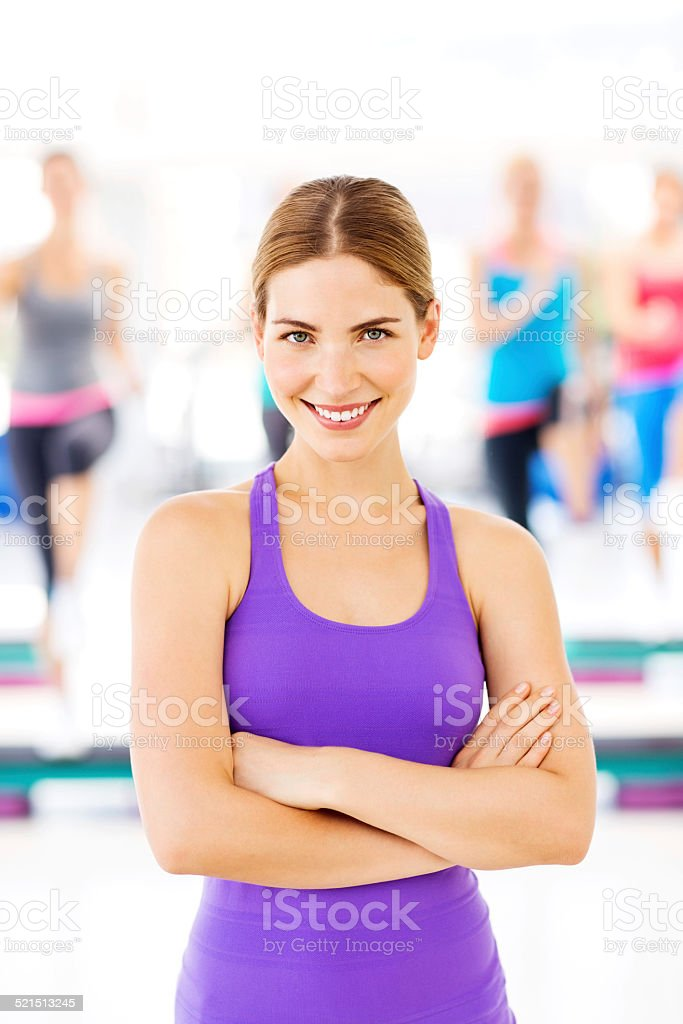 Aerobics Instructor With Customers Exercising In Background stock photo