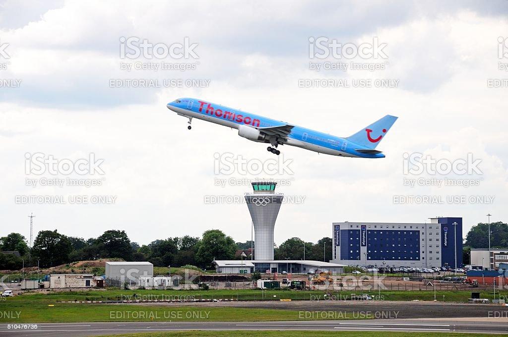 Aeroplane taking off over control tower, Birmingham. stock photo