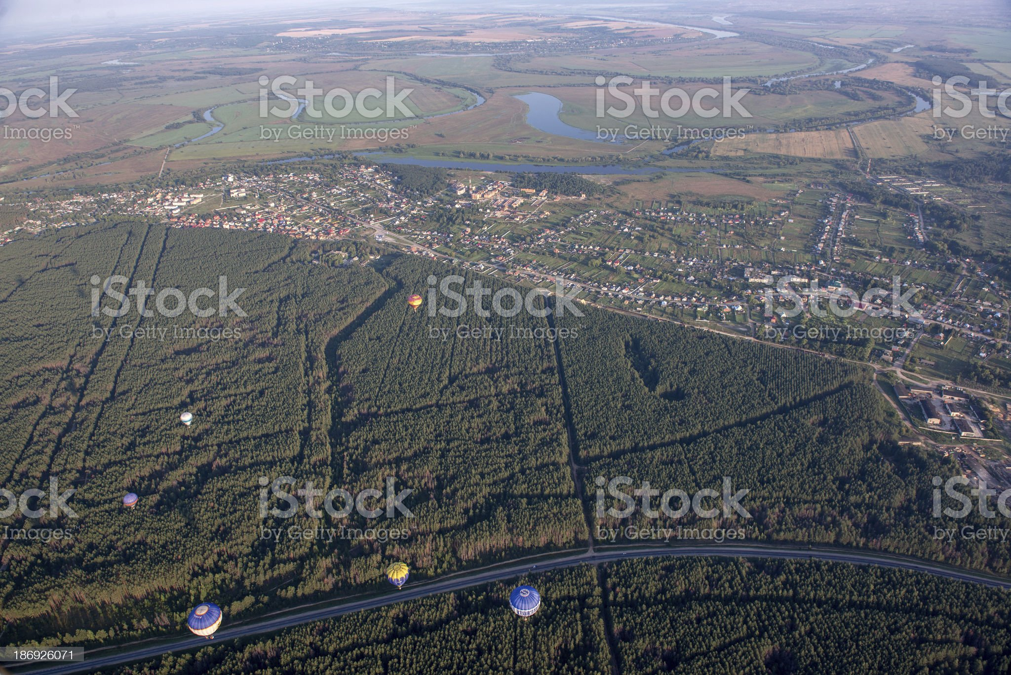 Aerostats in the air over fields and river. royalty-free stock photo
