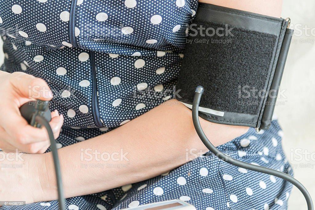 afemale arm and a tonometer measuring blood pressure, closeup stock photo